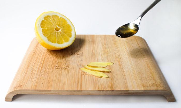 gingembre coupé avec un demi citron et une cuillère de miel sur une planche de bois